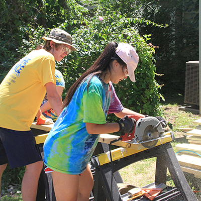 youth missioner uses circular saw to cut board