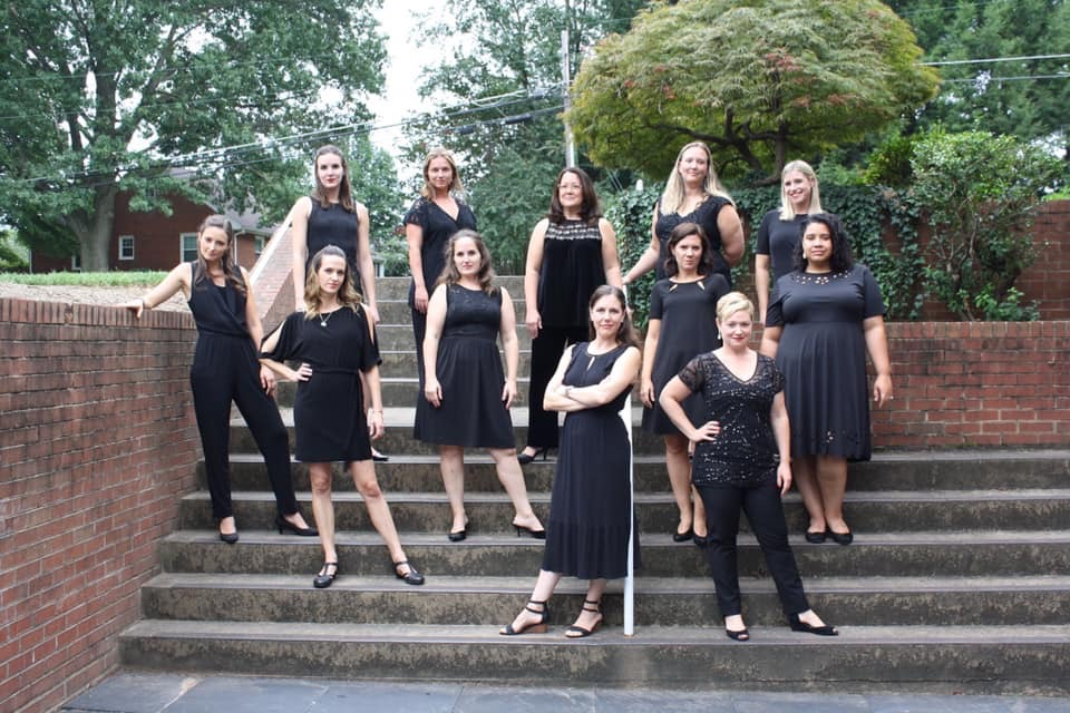 All female Caritas NoVa singers dressed in black standing on staircase