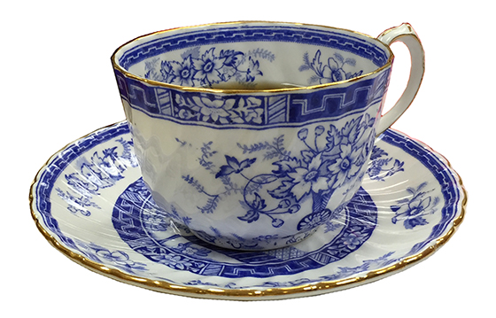 blue and white teacup and saucer on white background