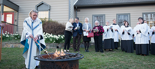 worshippers gathered on lawn as female clergy lights fire in fire pit