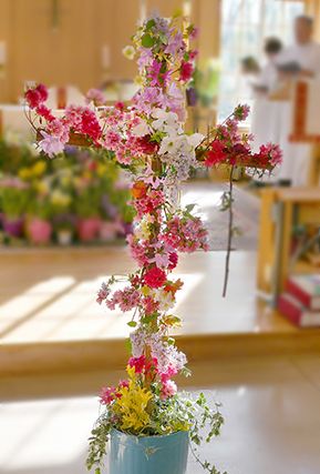 cross adorned with fresh flowers